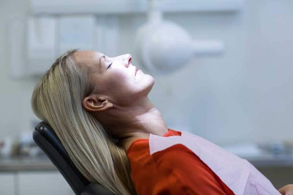 woman lay back in a dental chair with her eyes closed