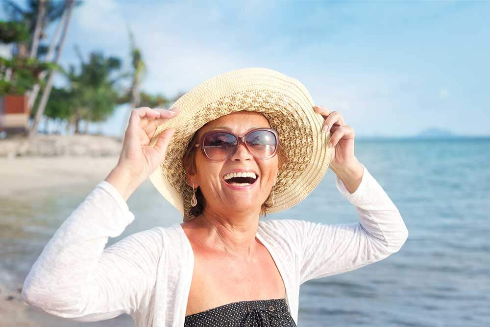 An older woman smiling on the beach and holding her hat on her head