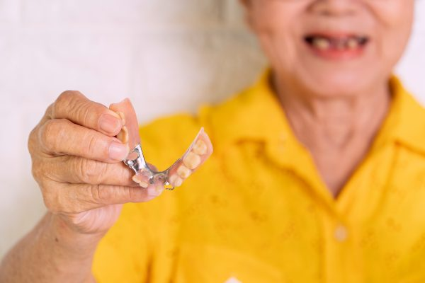 Older woman wearing yellow shirt holding her dentures
